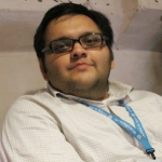 Aditya Kane reclining slightly backward in a chair, wearing glasses