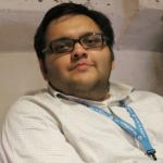 Aditya Kane reclining slightly backward in a chair, wearing glasses