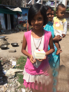 Little girl holding a piece of cake.