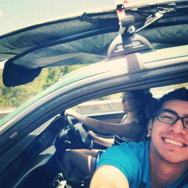 Car with surfboards on top. Brian leaning out the passenger window smiling while Ayla drives