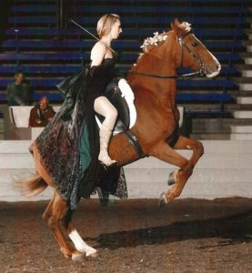 Erica Franz, in costume, on a rearing horse