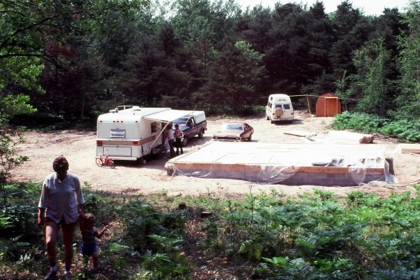 Photo of the foundation of a house with a trailer next to it in a clearing in the forest.
