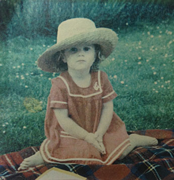 Photo of Tamsin, age 5, sitting on the lawn with a cute hat on