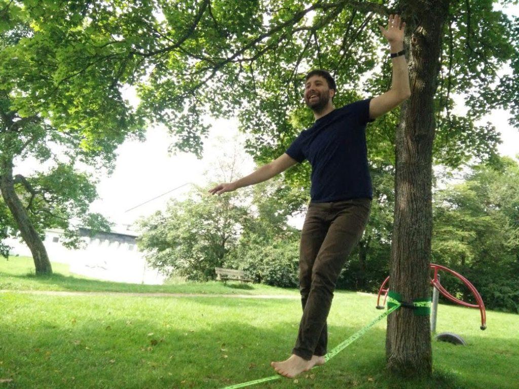 Gabor balancing on a narrow strap hung between two trees