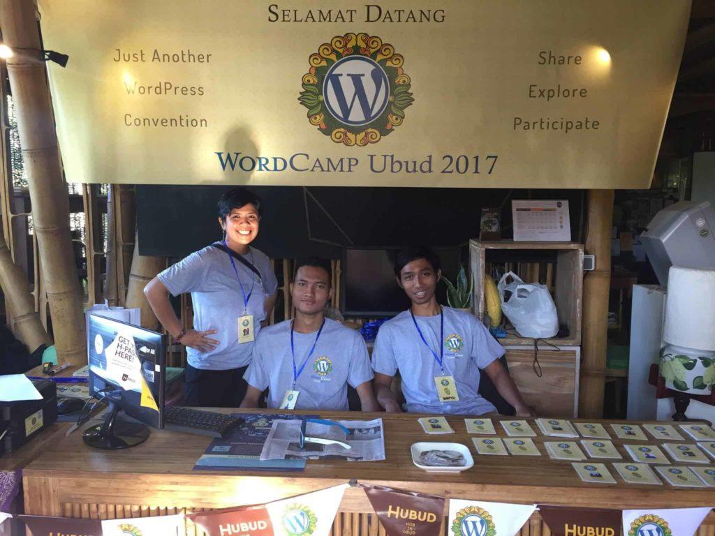 Devin and Pramana Adi Putra dan Wahyu Taufiq smiling from behind the registration table