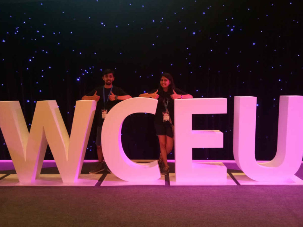 Giant WCEU logo with Dahara and a friend standing between the letters