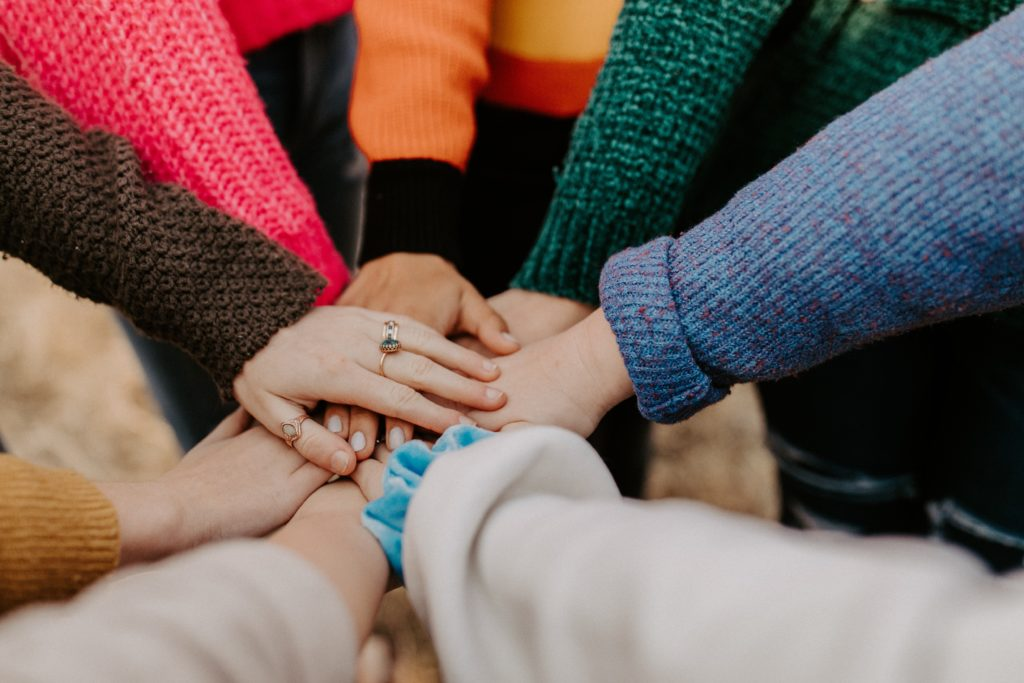 people with their hands in the middle of a circle together